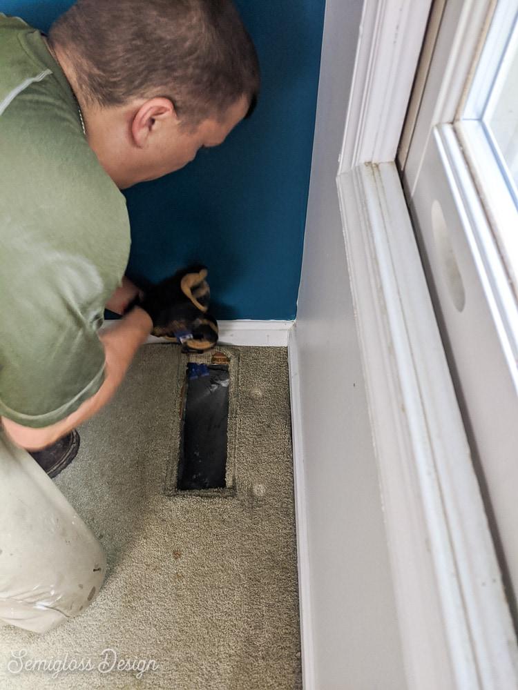 man removing carpet starting in corner of room