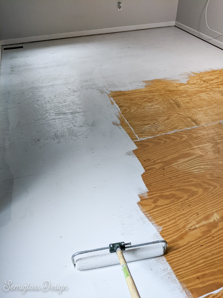 using large roller to paint floor