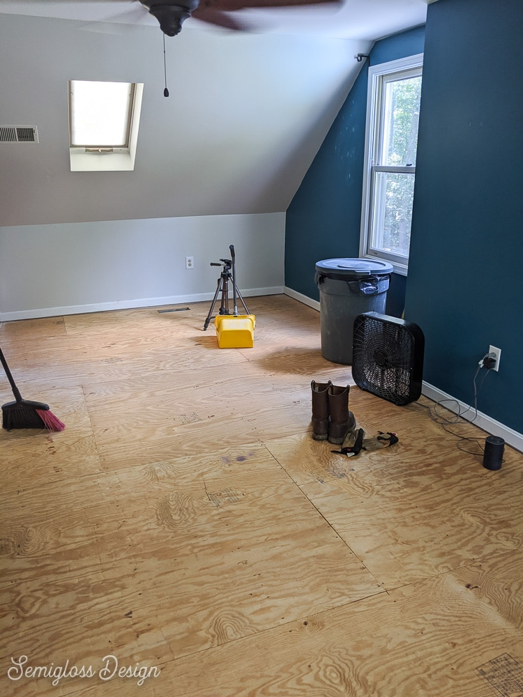 room with bare plywood floors after removing carpet