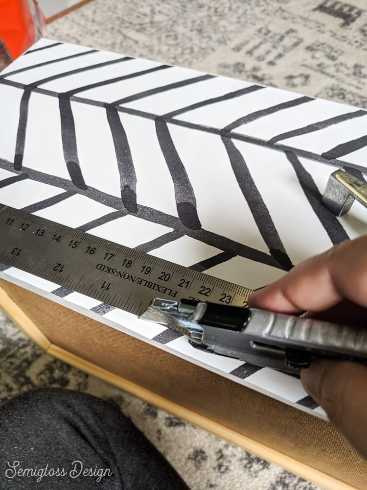cutting edges of wallpaper with utility knife