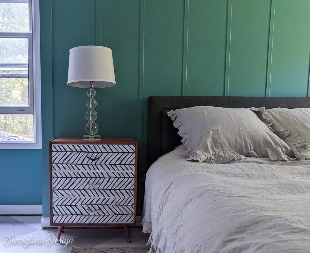 black and white pattern on dresser front in teal room with gray bed