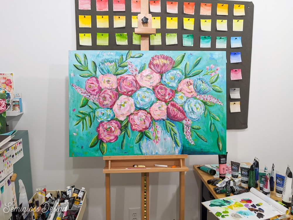 floral painting with pink and blue flowers on an aqua background