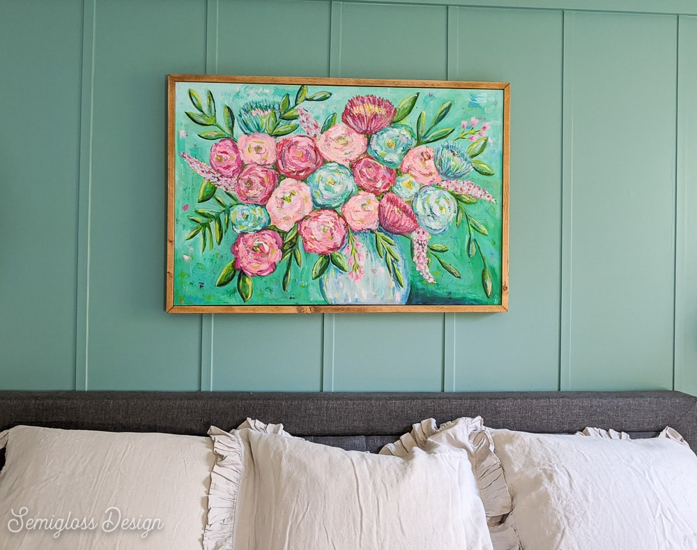 floral art on canvas with wood frame over gray bed