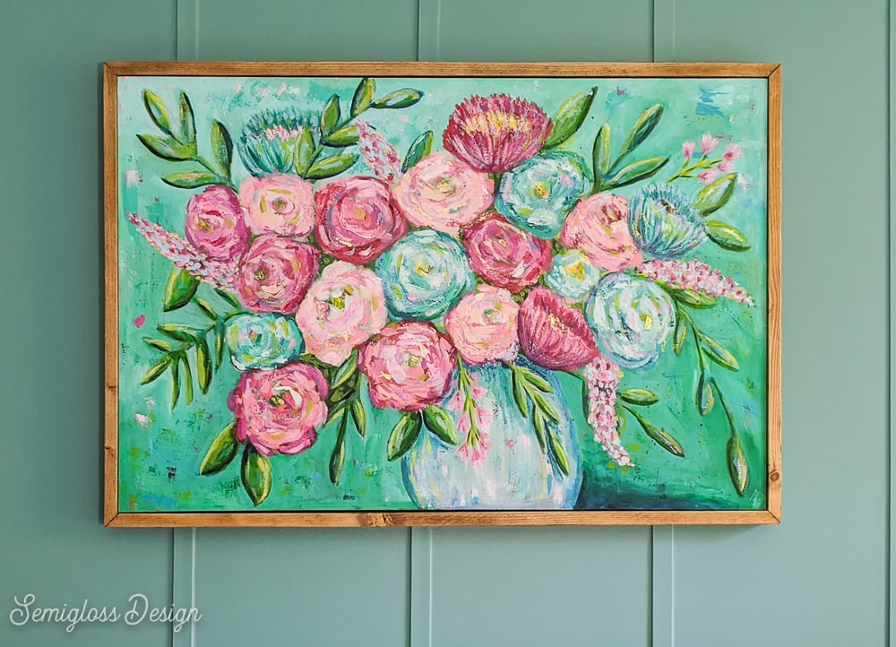 wood frame around floral painting with teal walls