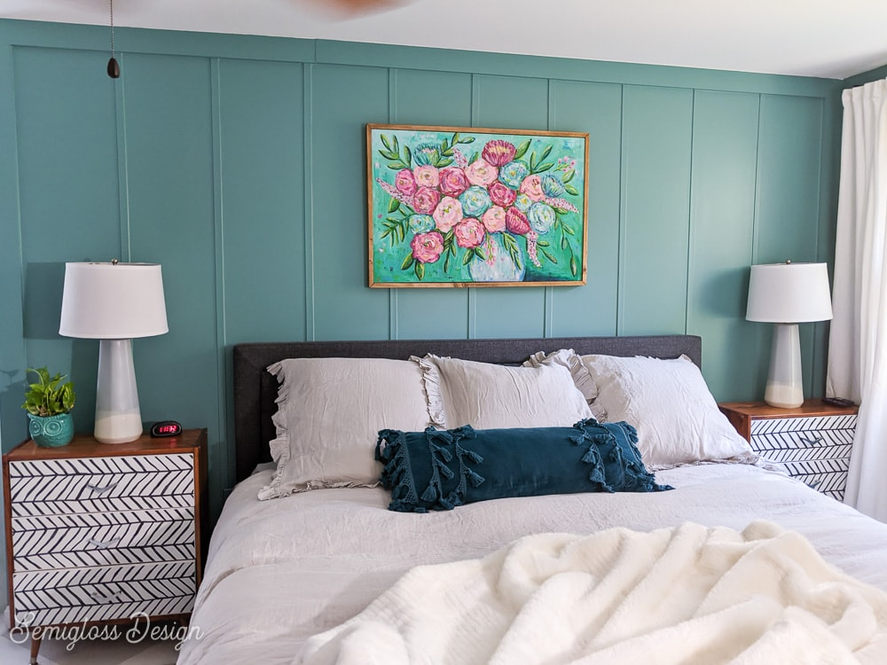 bed with gray bedding against teal walls with floral painting