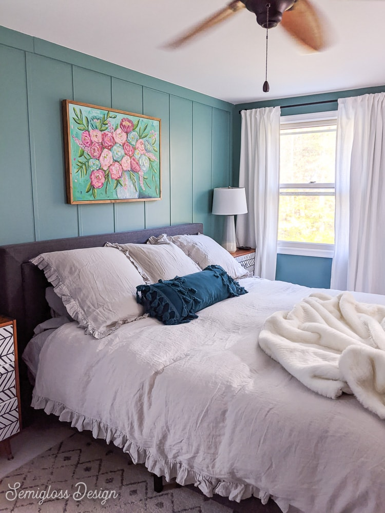 cozy master bedroom with fluffy gray bedding and teal walls