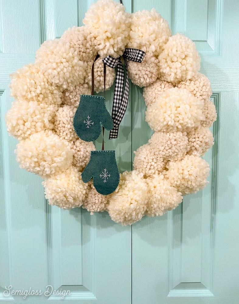 white fluffy yarn ball wreath on aqua door