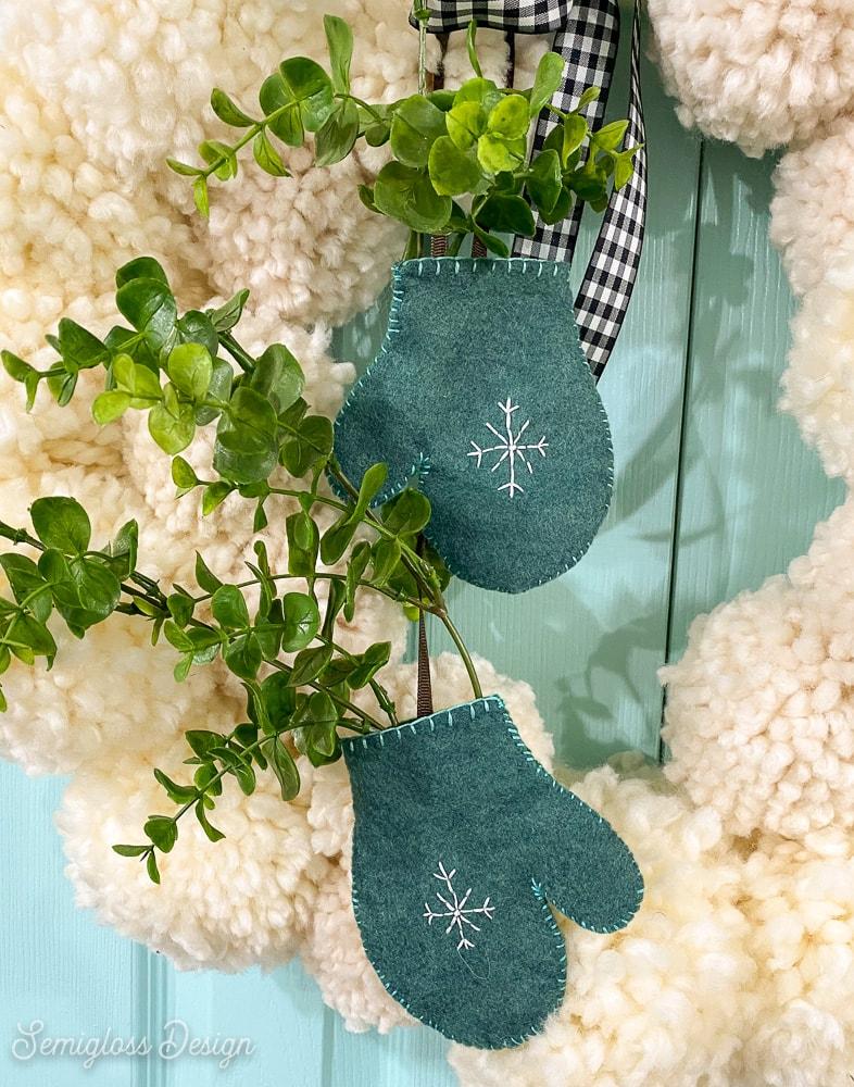 adding greenery to felt mitten on pom pom wreath
