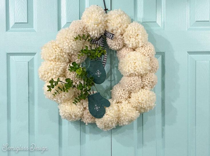 white pom pom wreath on aqua doors