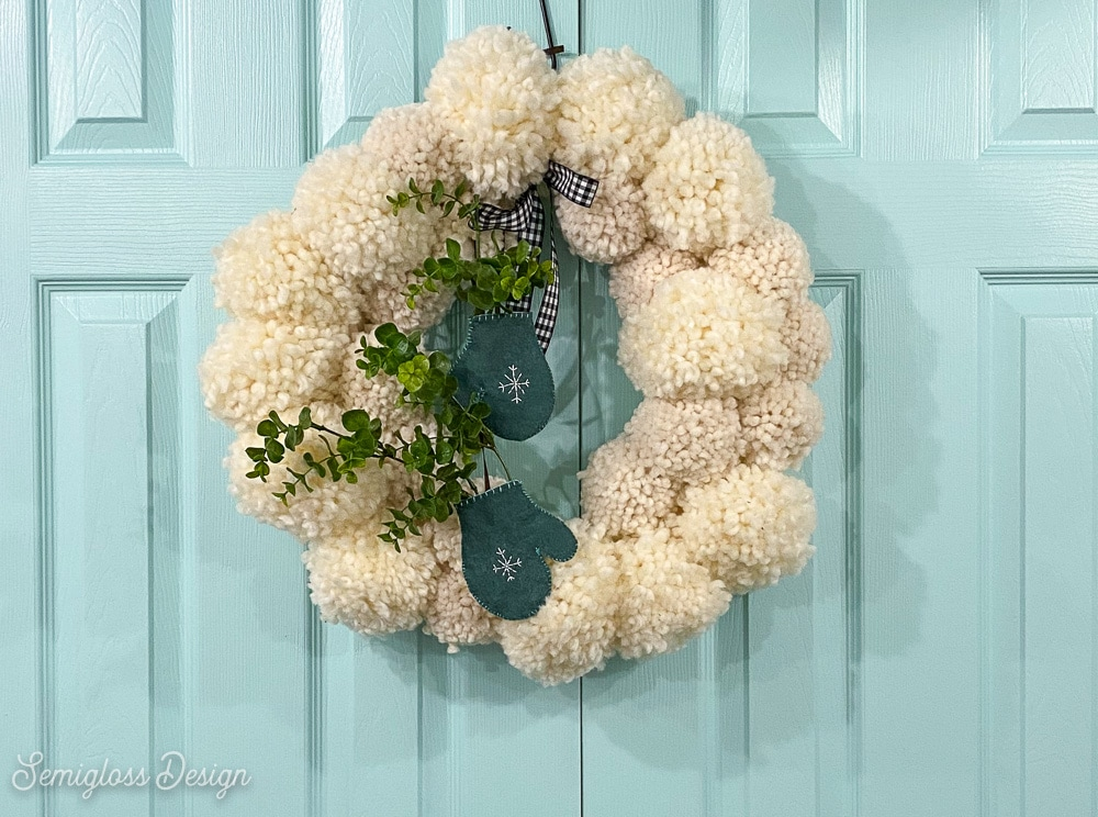 white pom pom wreath on aqua doors