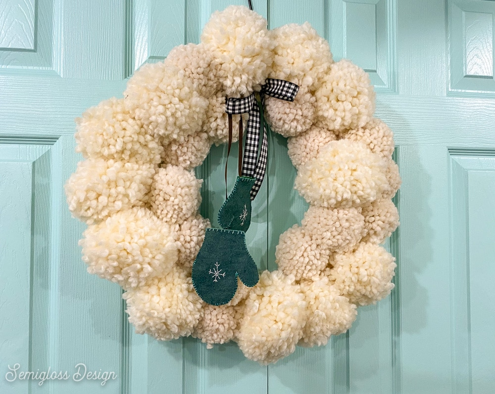 adding mittens and a bow to pom pom wreath