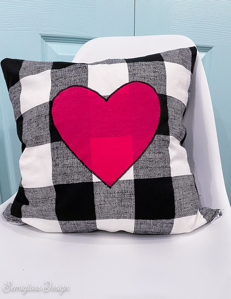black and white buffalo check pillow with pink heart on white chair