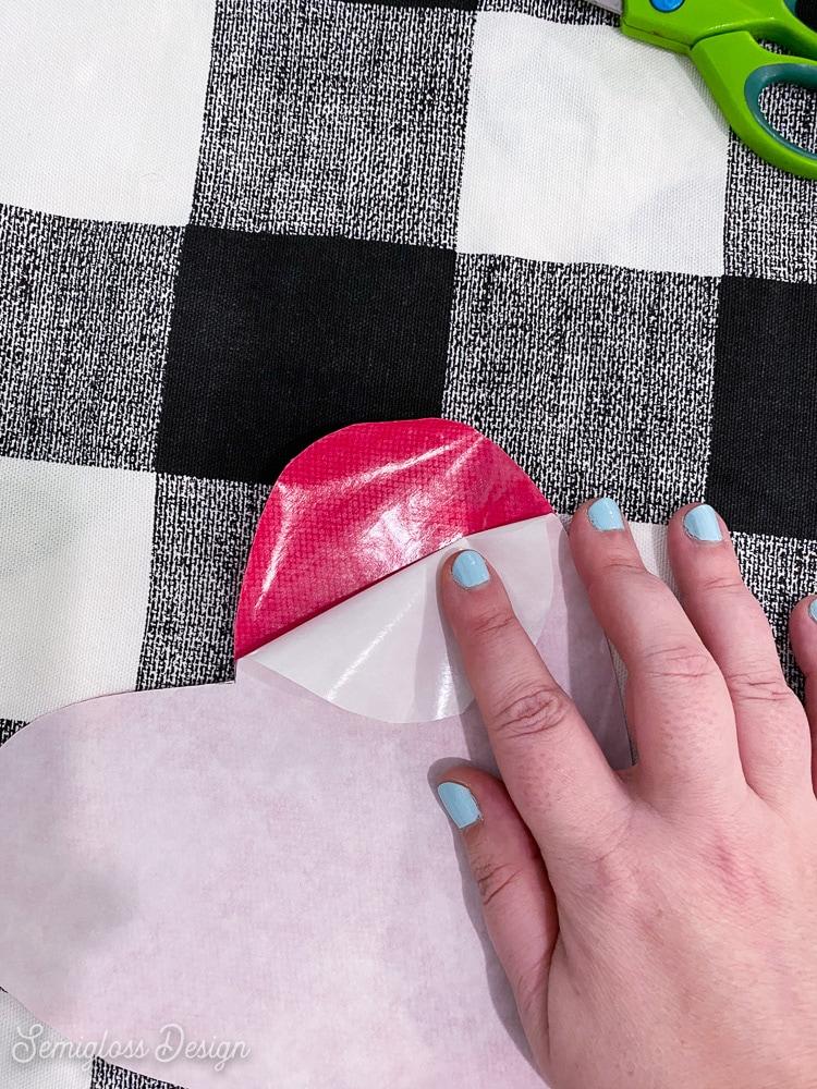 peeling away paper for iron-on adhesive sheet