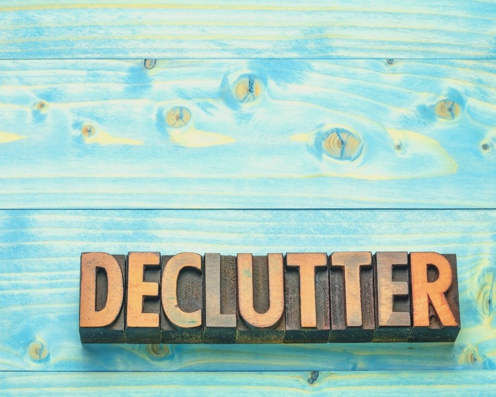 aqua wood background with stamp blocks that say declutter