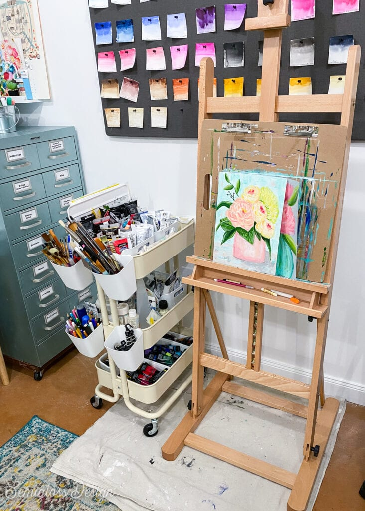 easel with flower painting and cart with paints