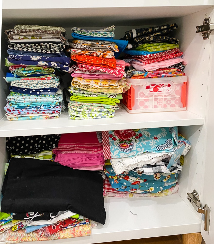 stacks of quilting fabric in cabinet