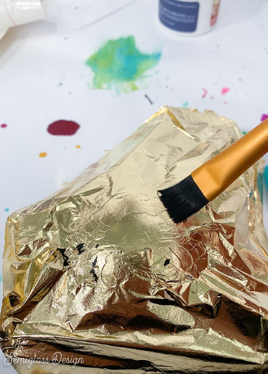 using a paintbrush to burnish gold leaf