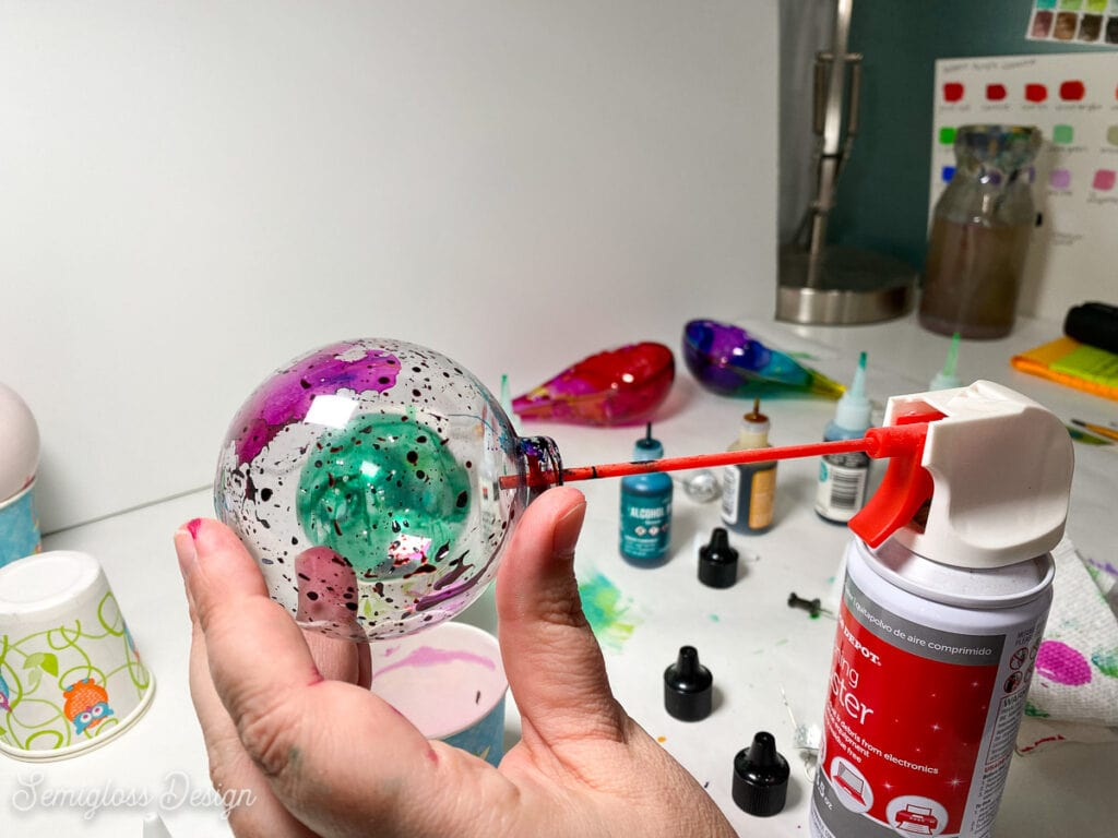 spraying alcohol ink in ornament with canned air