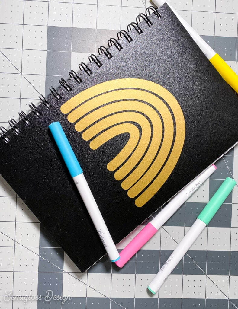 sketchbook with gold decal and pens