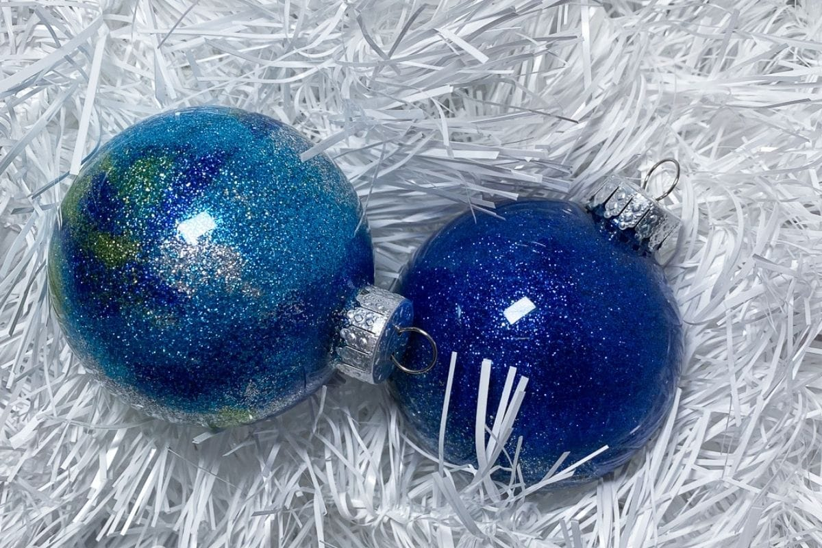 blue glitter christmas ornaments on white tinsel