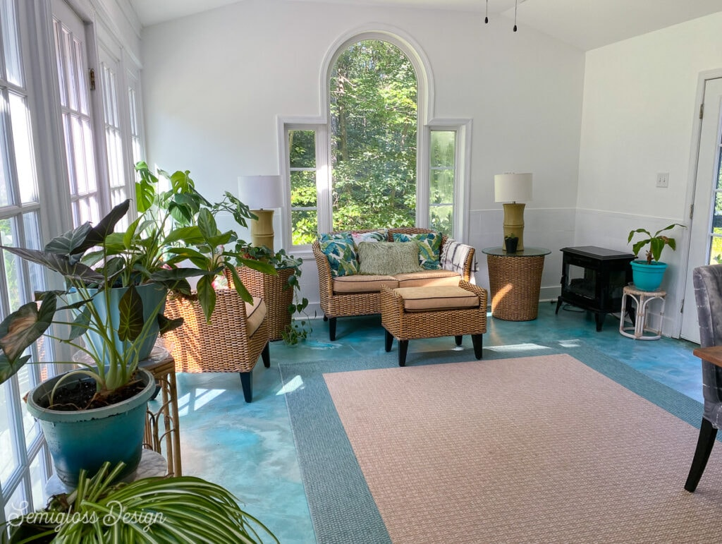 sunroom with teal floor and wicker furniture