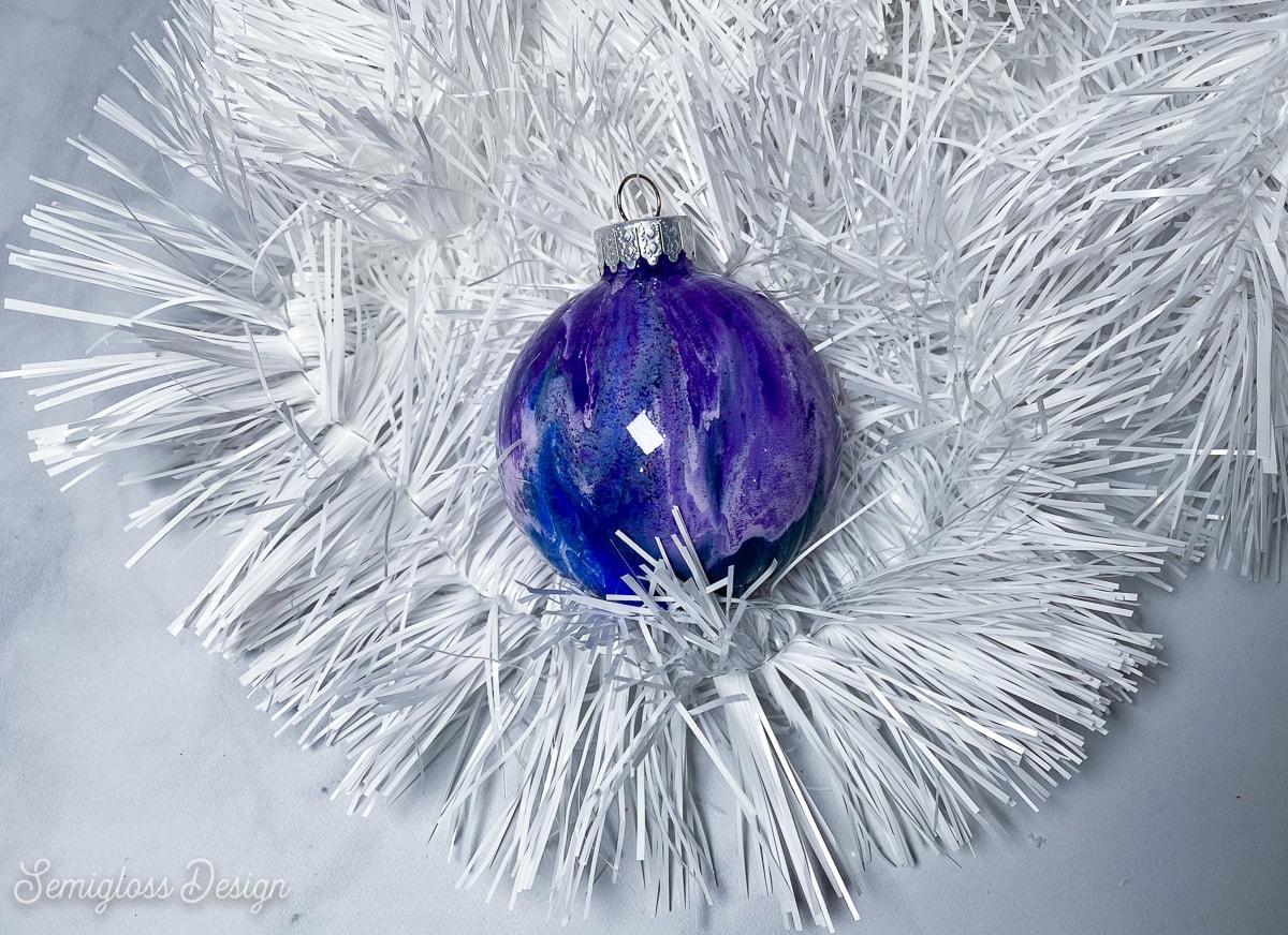 purple paint swirl galaxy ornament on white tinsel