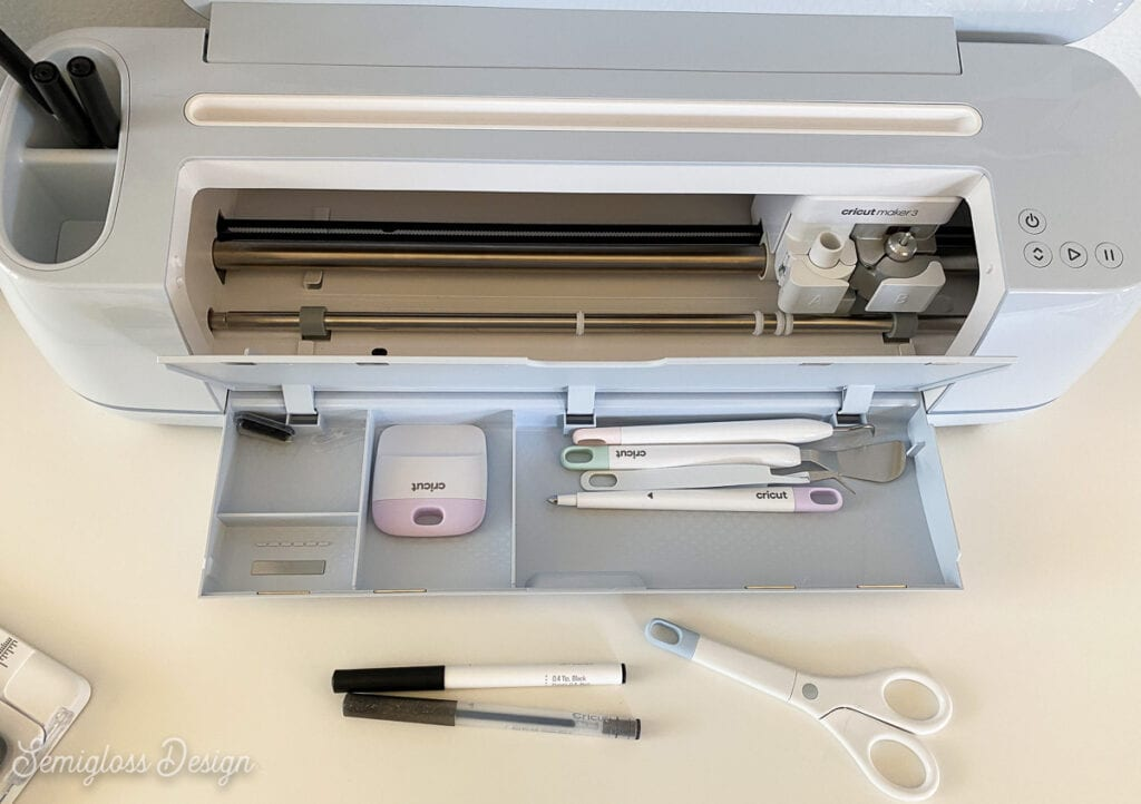 Cricut maker open with weeding tools in storage