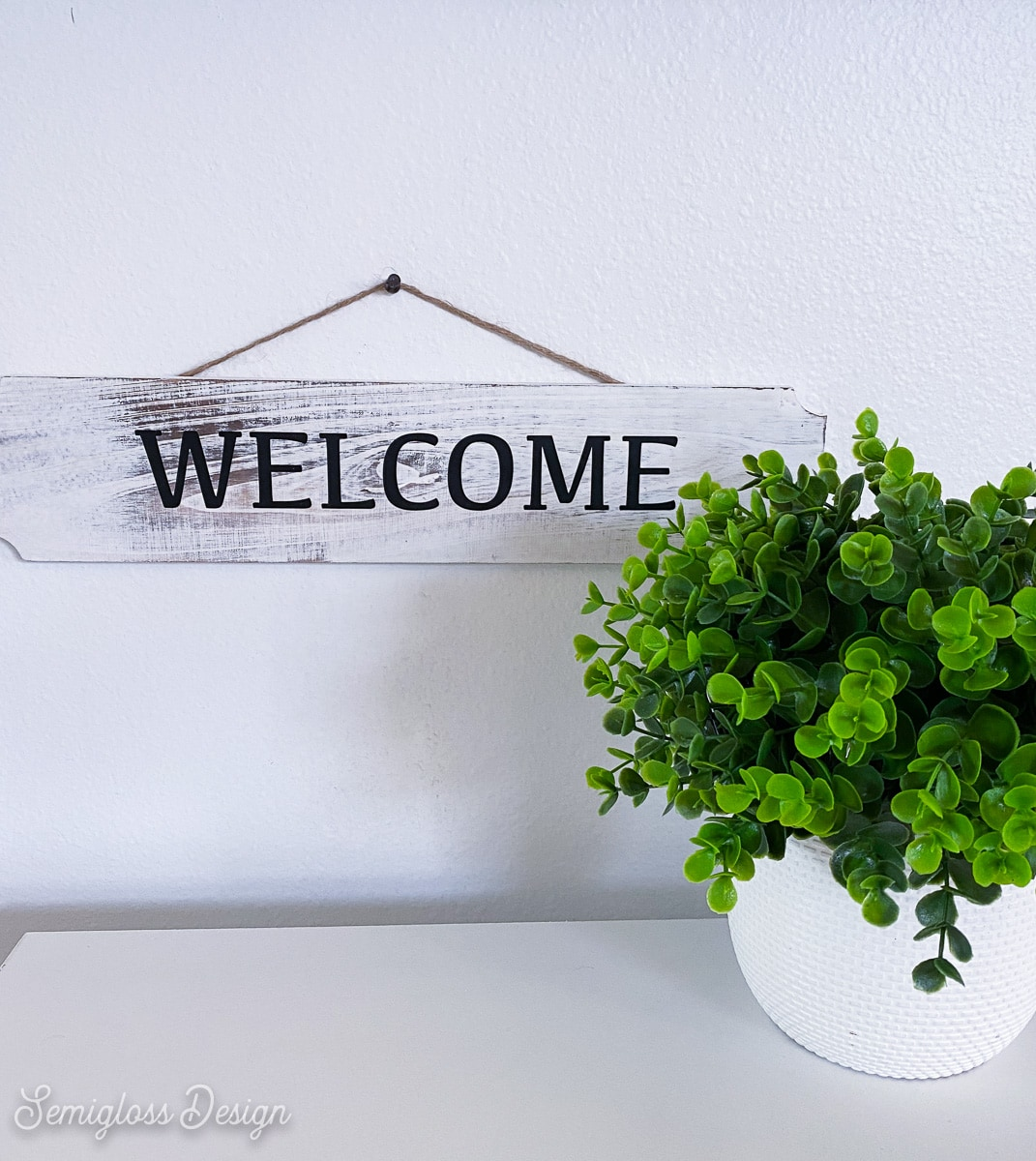 welcome sign with plant