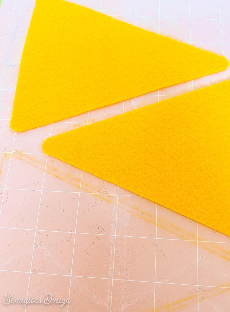 yellow felt triangles on pink cricut mat