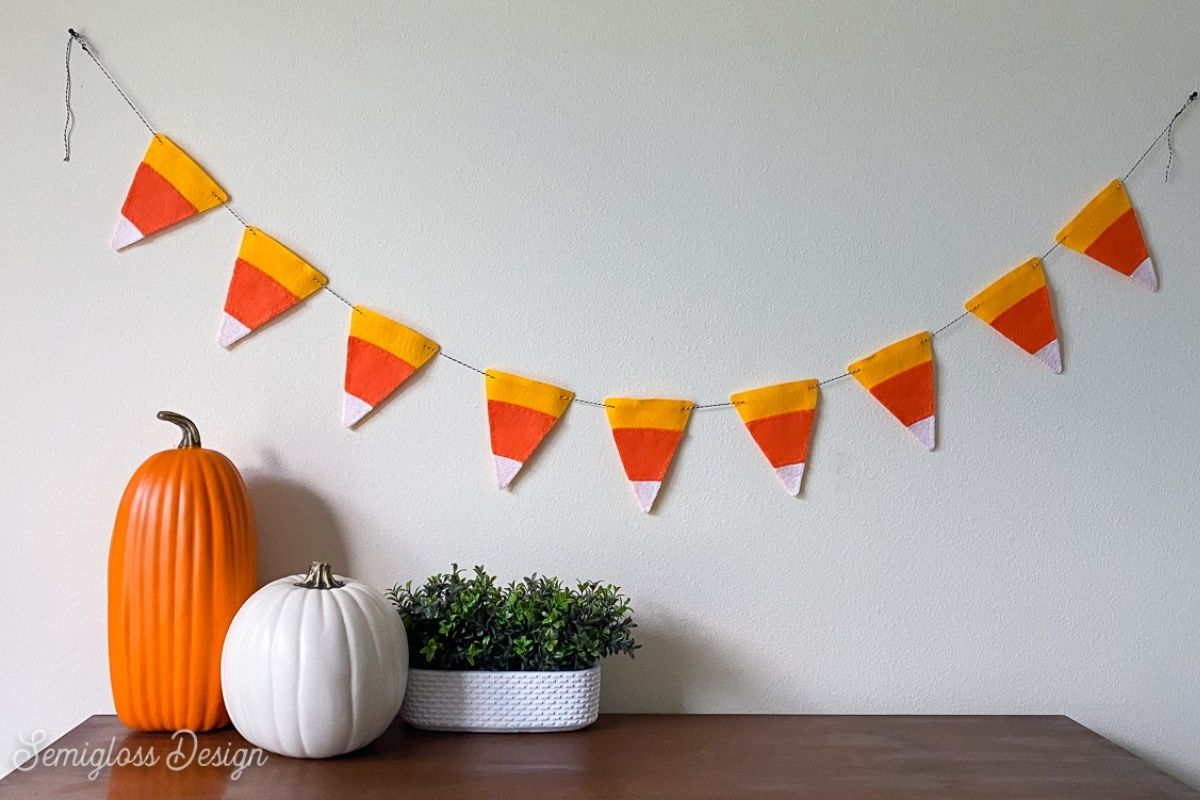 felt candy corn banner on white wall with pumpkins