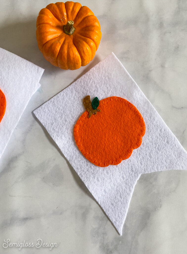 pumpkin sewn onto white felt flag