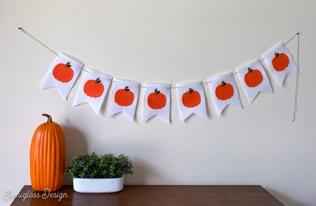 pumpkin banner hung over dresser with pumpkin and plant